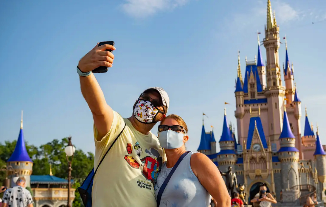 A couple with a mask on is taking a photo with signature Disneyland's castle.