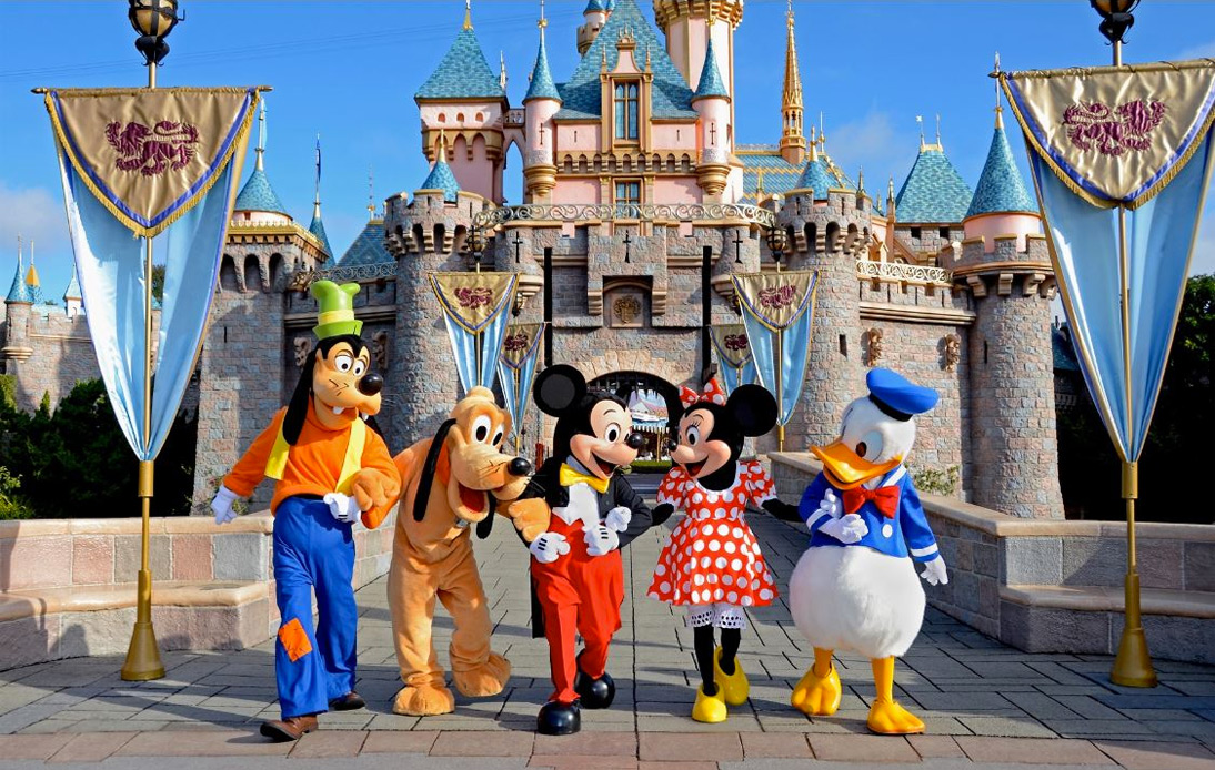 The mascot of Mickey Mouse and friends in front of Disneyland's castle.