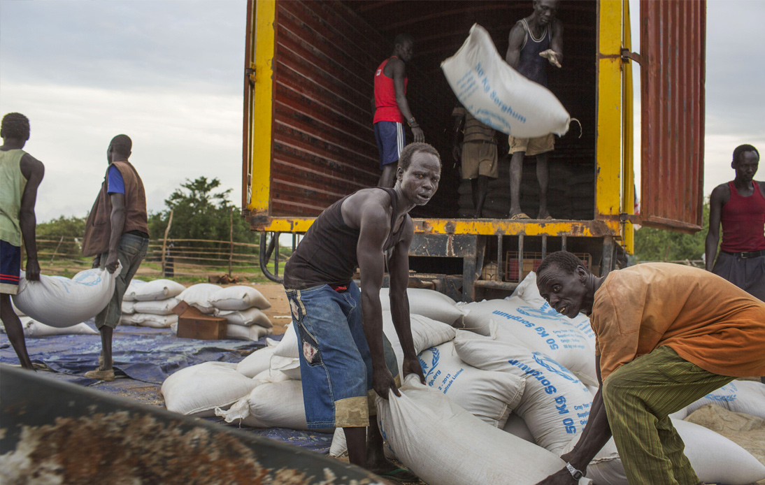 workers offload sacks of cereals from the World Food Program (WFP) from a truck in Minkaman, South Sudan